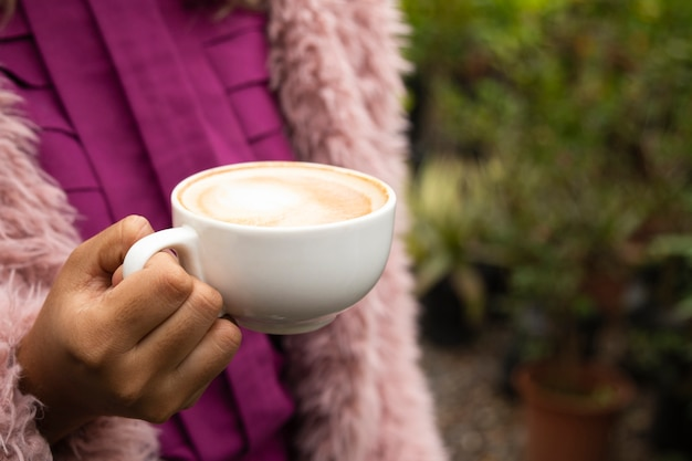 Primer plano de mujer sosteniendo una taza de café