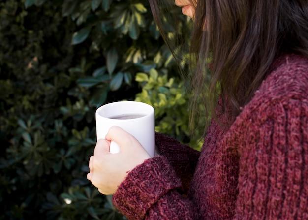 Primer plano de una mujer sosteniendo la taza de té de hierbas blancas