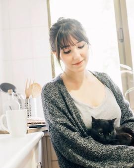 Primer plano de una mujer con su gatito en la cocina