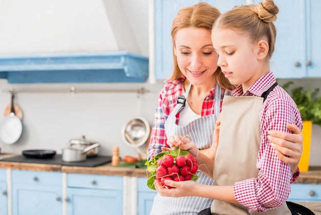 Primer plano de la mujer y su hija sentada en la cocina