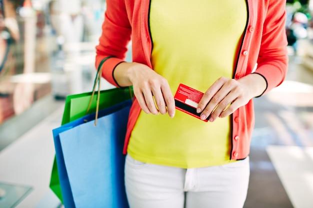 Primer plano de mujer sujetando una tarjeta de crédito