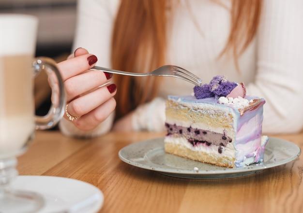 Primer plano de una mujer con un tenedor sobre la deliciosa rebanada de pastel de arándanos en un plato sobre la mesa de madera