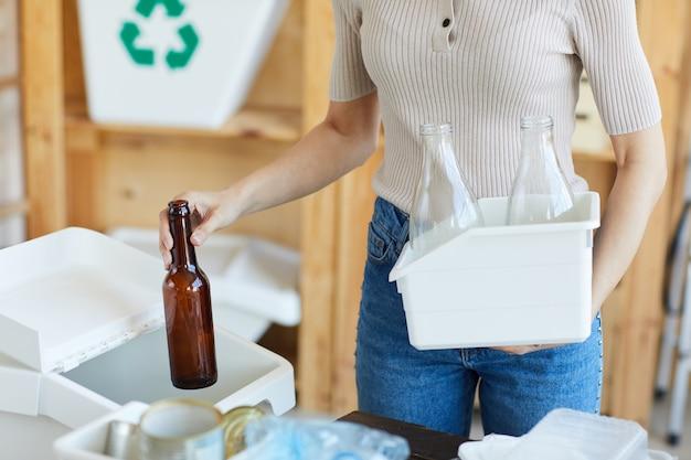 Primer plano de mujer tirando la botella de vidrio en el recipiente