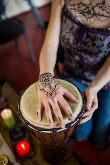Primer plano de una mujer tocando el bongo drum con tatuaje mehndi en su mano