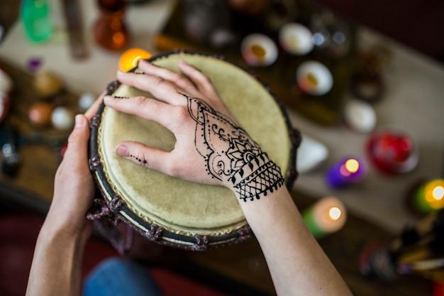 Primer plano de mujer tocando tambor con tatuaje mehndi en su mano