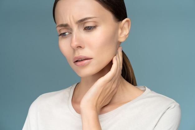 Primer plano de una mujer triste enferma que controla los ganglios linfáticos, resfriado, que sufre de problemas de garganta