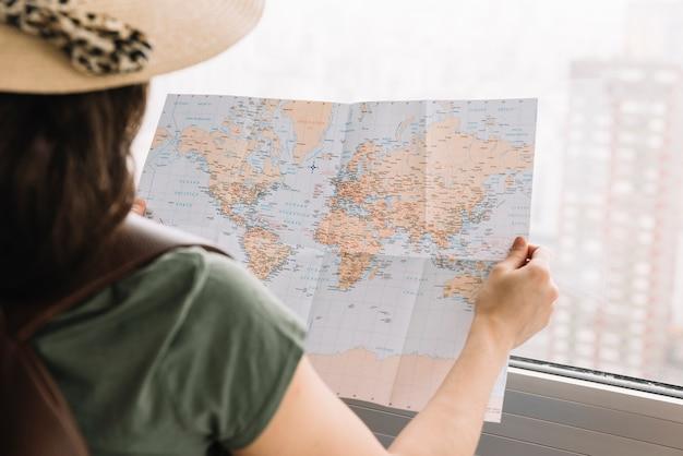 Primer plano de una mujer turista leyendo el mapa cerca de la ventana
