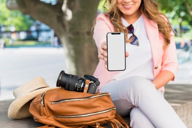 Primer plano de mujer turista sentada al lado de la bolsa; sombrero y cámara mostrando su pantalla de teléfono móvil