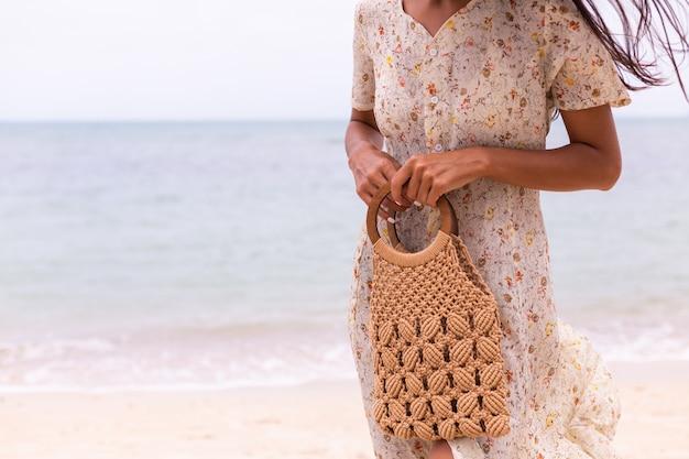 Primer plano de mujer en vestido de vuelo de verano ligero con bolso tejido en la playa, mar de fondo.