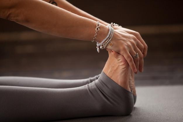 Primer plano de mujer yogui en ejercicio de curva hacia adelante sentado