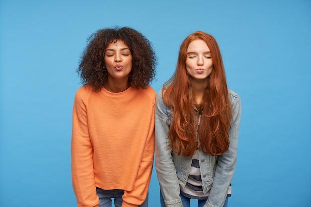 Primer plano de mujeres atractivas jóvenes positivas que mantienen los ojos cerrados mientras doblan los labios en un beso al aire, manteniendo las manos hacia abajo mientras están de pie contra la pared azul