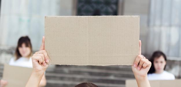 Primer plano de mujeres con carteles de cartón en protesta