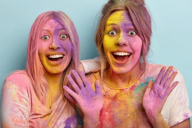 Primer plano de mujeres jóvenes felices que se divierten con polvos de colores en el festival de holi, sonríen ampliamente, tienen caras multicolores, escuchan increíbles buenas noticias, aisladas sobre una pared azul. día festivo