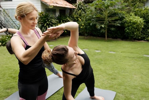 Primer plano de mujeres practicando yoga en una clase al aire libre, el entrenador corrige la postura de la mujer de negro