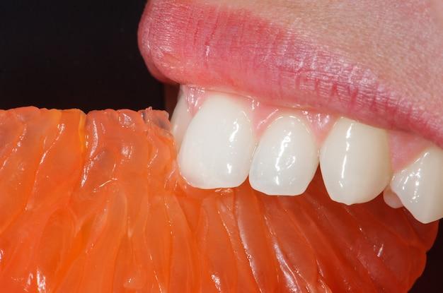 Primer plano de naranja en la boca de la mujer.