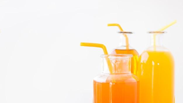 Primer plano de una naranja y botellas de jugo de mango con pajitas aisladas sobre fondo blanco