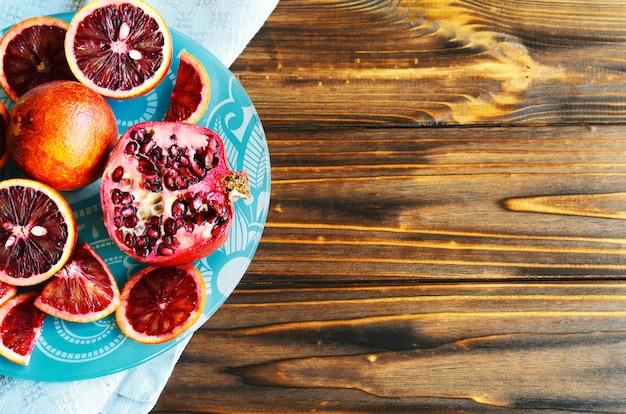 Primer plano de naranjas rojas de sangre siciliana cortadas y en rodajas, maduras y sabrosas con copyspace, madera natural