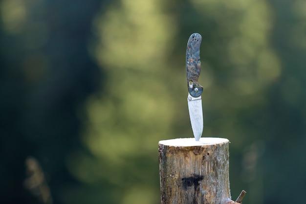 Primer plano de navaja plegable con mango de plástico pegado verticalmente en el tocón de un árbol al aire libre