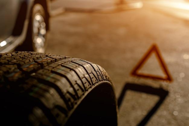 Primer plano de un neumático de automóvil. el conductor debe reemplazar la rueda vieja con una de repuesto.