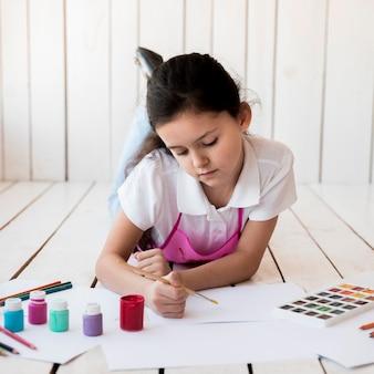 Primer plano de una niña acostada sobre tablones de madera pintando sobre el papel blanco la brocha