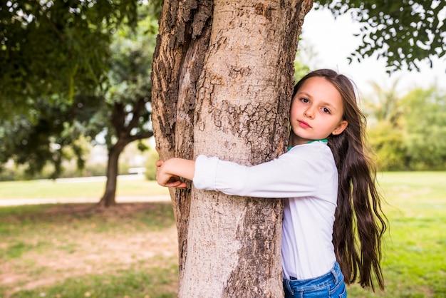 Primer plano de una niña adorable abrazando el tronco del árbol