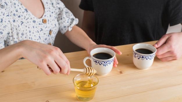 Primer plano de una niña agregando miel en la taza de té en el escritorio