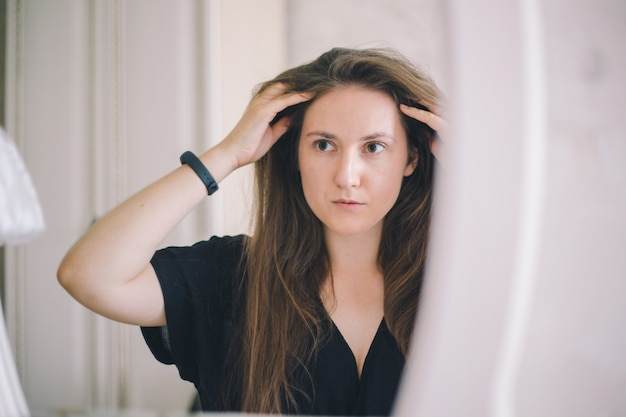 El primer plano de una niña de aspecto europeo alisa el cabello en un espejo en una habitación de hotel luminosa