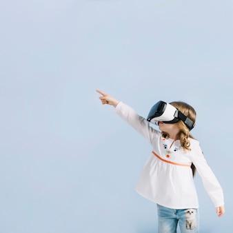 Primer plano de una niña con auriculares de realidad virtual apuntando su dedo contra el fondo azul