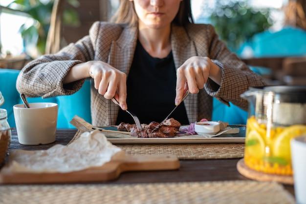 Primer plano de niña con cubiertos en el restaurante comiendo carne asada
