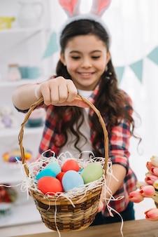 Primer plano de una niña dando coloridos huevos de pascua canasta