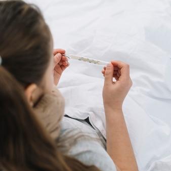 Primer plano de una niña enferma que controla la temperatura en el termómetro