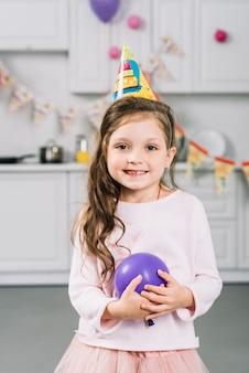 Primer plano de una niña feliz con globo morado