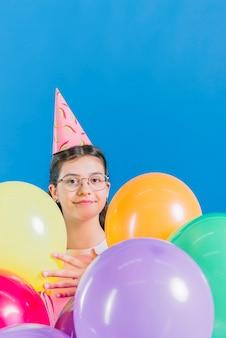Primer plano de una niña con globos de colores sobre fondo azul