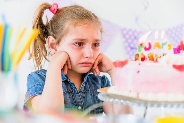Primer plano de una niña llorando mirando pastel de cumpleaños
