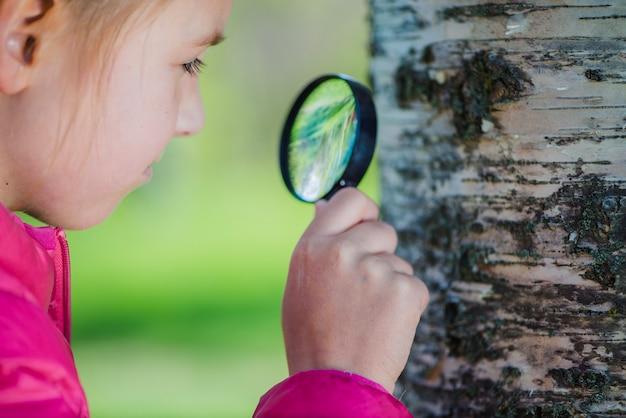 Primer plano de niña mirando con lupa un tronco