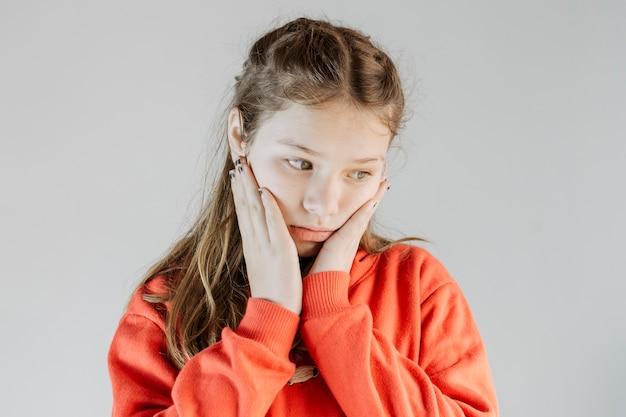 Primer plano de una niña molesta sobre fondo gris