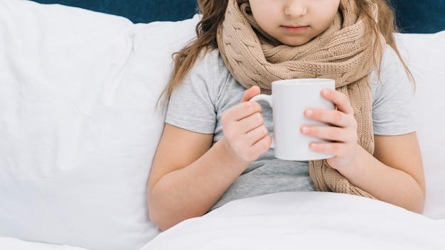 Primer plano de una niña paciente con una bufanda alrededor del cuello sosteniendo una taza de café con leche