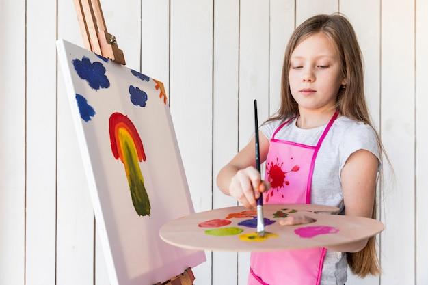 Primer plano de una niña con el pelo largo y rubio pintado en el lienzo de pie contra la pared de madera blanca