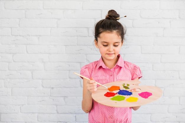 Primer plano de una niña de pie contra la pared de ladrillo blanco mezclando el color en la paleta