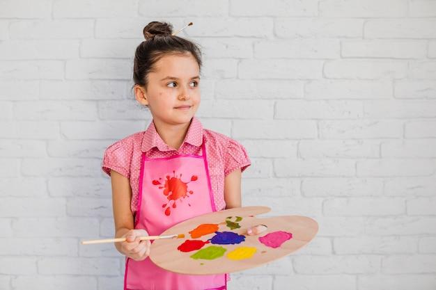 Primer plano de una niña de pie contra la pared de ladrillo blanco con paleta y pincel mirando lejos