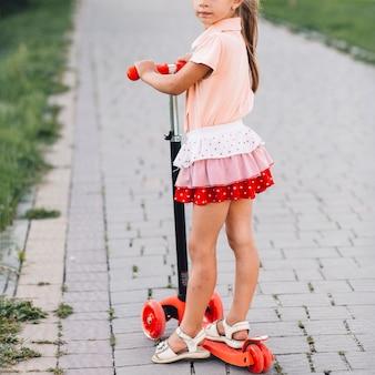 Primer plano de una niña de pie en scooter de empuje en el parque