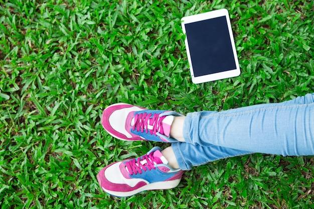 Primer plano, niña, piernas, tableta, hierba