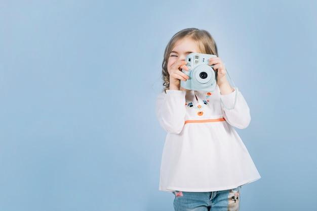 Primer plano de una niña que captura la foto con una cámara instantánea contra el fondo azul