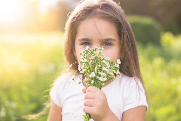Primer plano de una niña que huele a flores blancas
