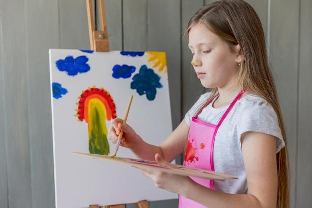 Primer plano de una niña que mezcla la pintura con un cepillo de pie delante de un lienzo pintado