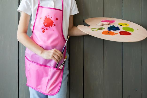 Primer plano de una niña que sostiene la paleta en la mano quitando el pincel del delantal rosado de pie contra la pared de madera gris