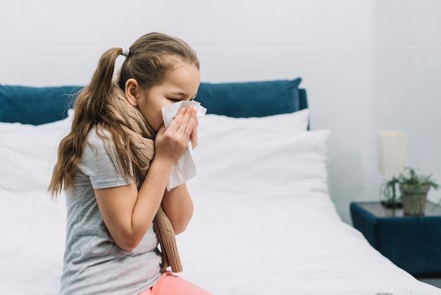 Primer plano de una niña que tiene frío soplando su nariz que moquea con tejido