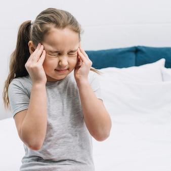 Primer plano de una niña sentada en la cama que tiene dolor severo en dolor de cabeza