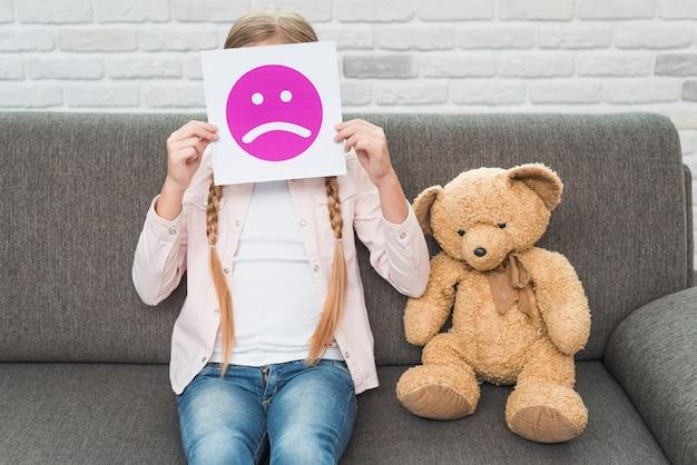 Primer plano de una niña sentada con peluche sosteniendo papel de emoticonos de cara triste frente a su cara