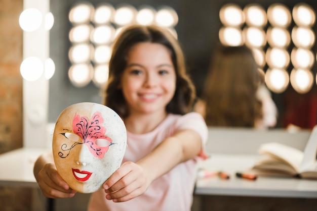 Primer plano de una niña sentada en la sala de maquillaje con máscara veneciana